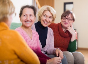 Happy senior friends chatting in living room at home